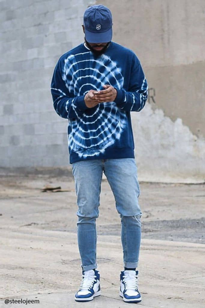 man wearing adire top and jeans