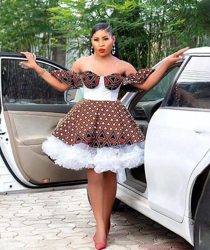 lady rocking ankara dress with white net beside side a car