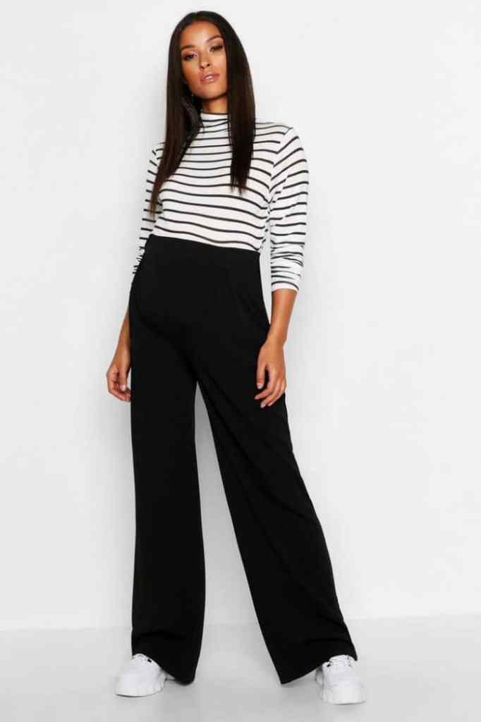 lady rocking black and white stripped turtle neck top with black palazzo pants and sneakers