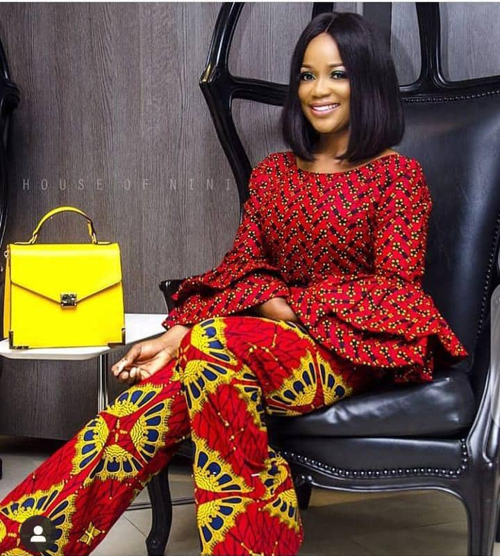 smiling lady wearing peplum top and trouser in different ankara prints