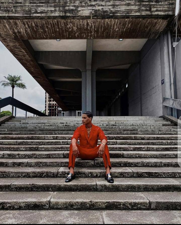 Denola Grey in an orange outfit with b;lack shoes