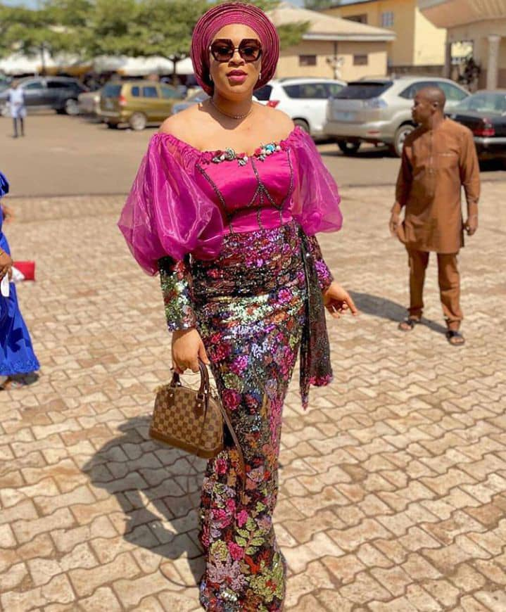 lady wearing ankara and organza long dress with gele