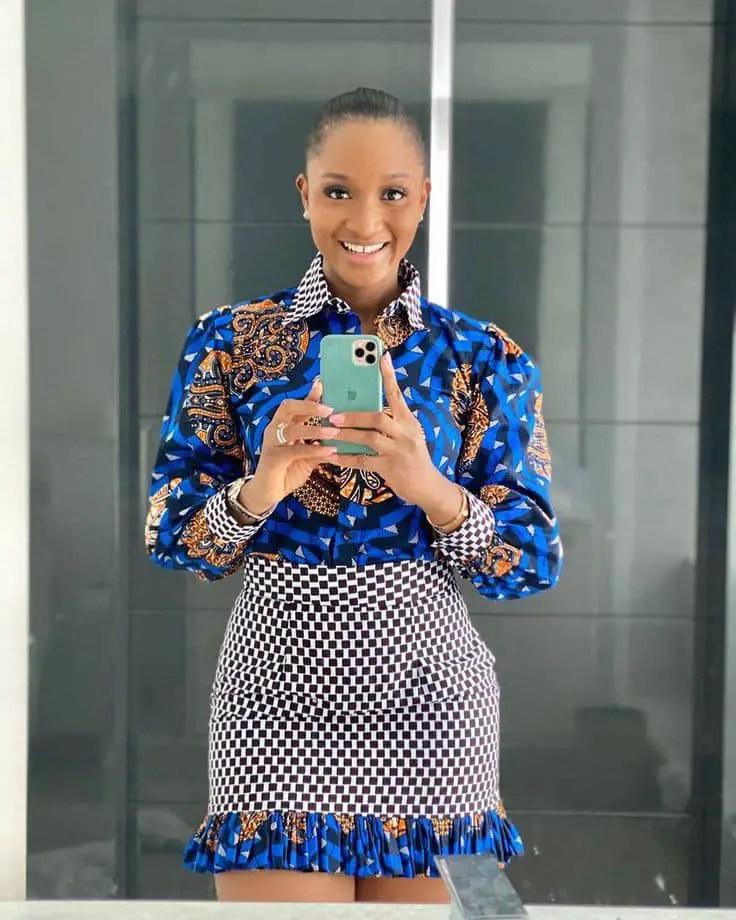 smiling lady wearing ankara shirt and skirt taking a mirror photo