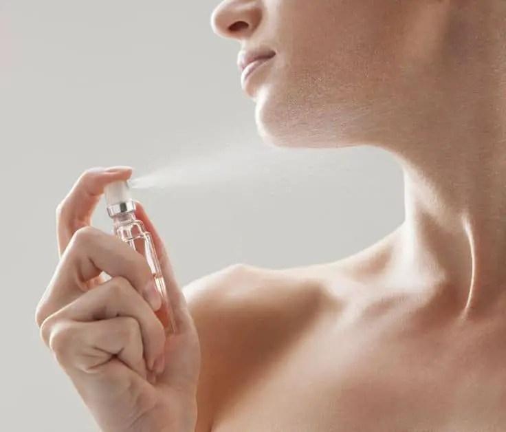 Lady applying perfume on her skin