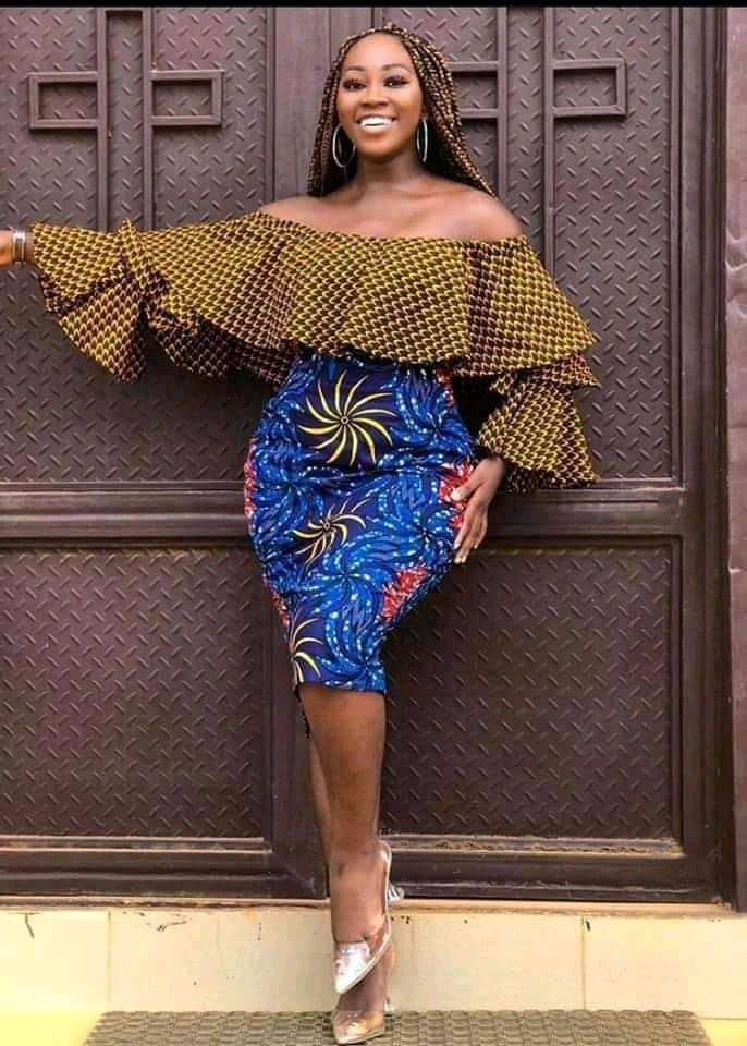 smiling lady wearing ankara top with skirt