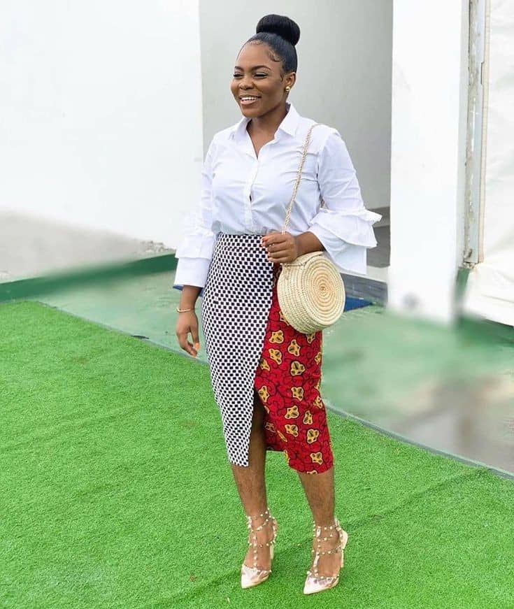smiling lady wearing white shirt and ankara skirt