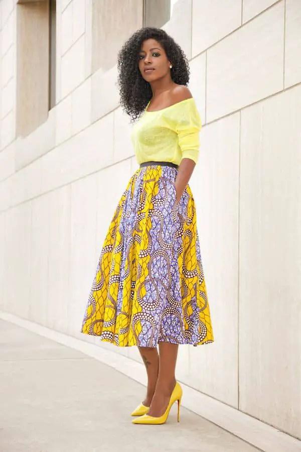 lady wearing yellow top and ankara flare skirt