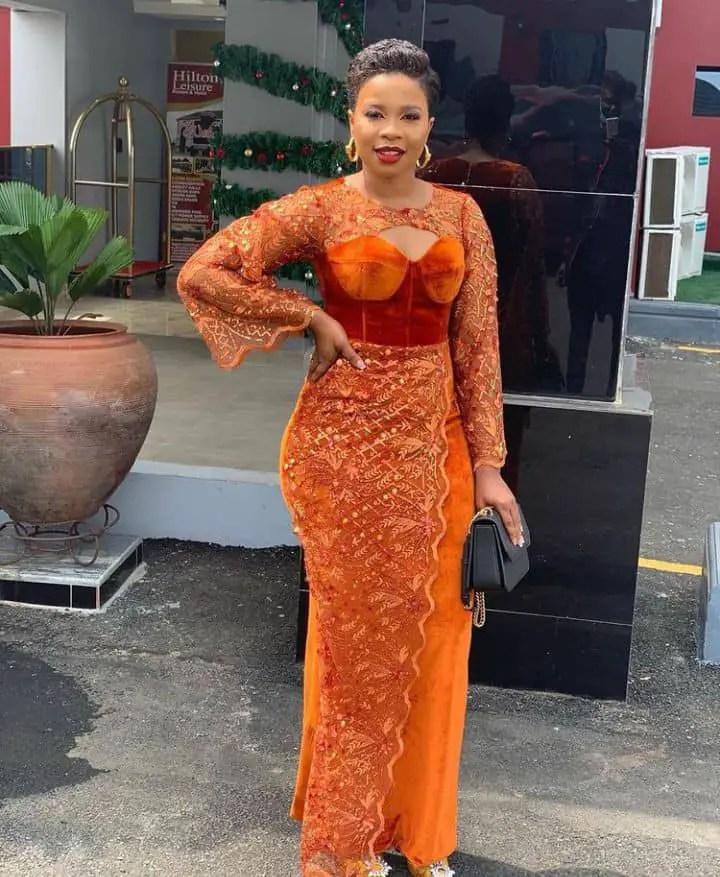 lady inn an orange dress aso ebi for owambe