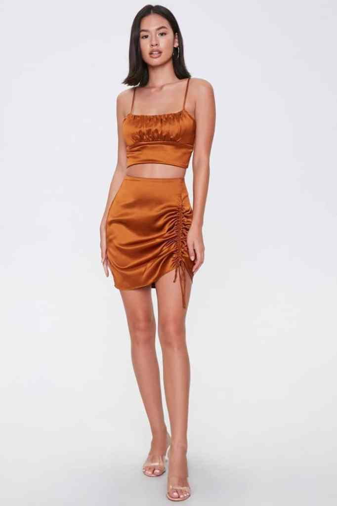 lady wearing gold matching set top and mini skirt