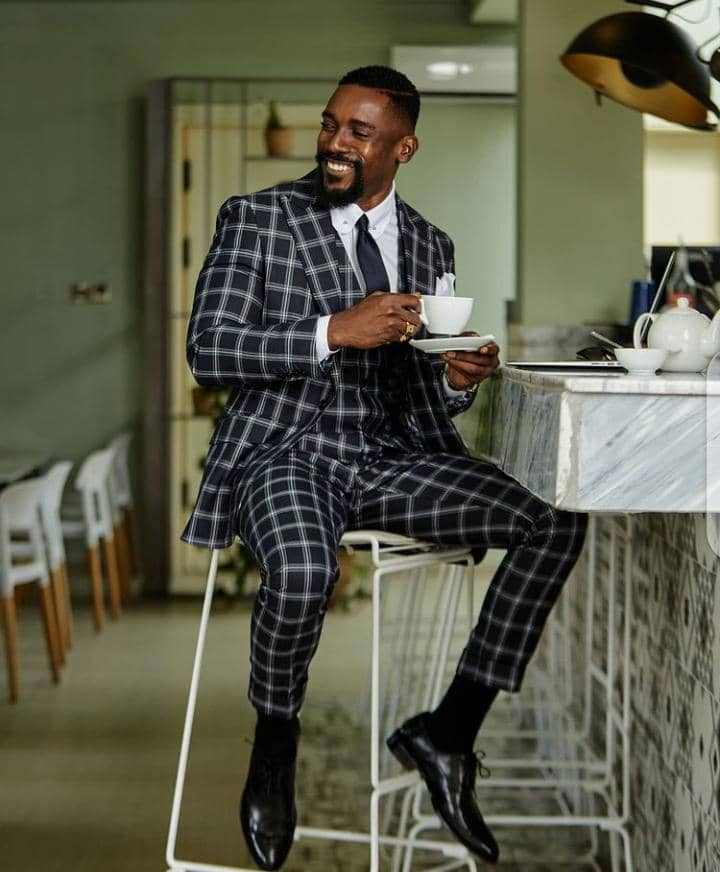 man smirking in suit and tie, sipping coffee