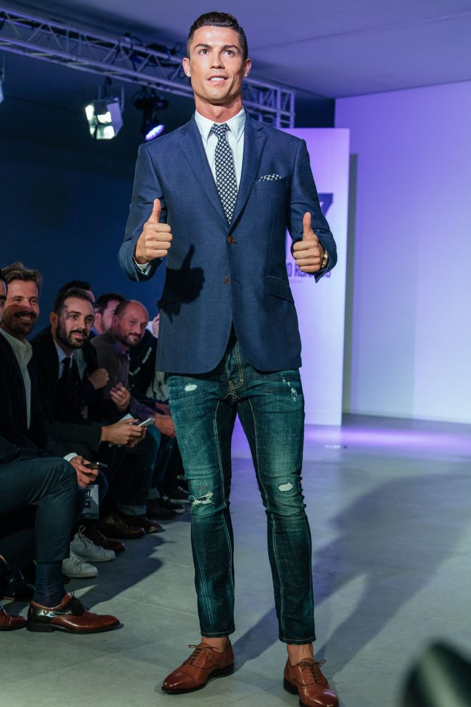 Christiano Ronaldo wearing suit and tie with jeans on the runway