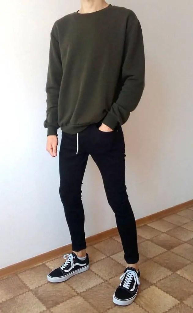 man wearing wearing sweater with black skinny jeans