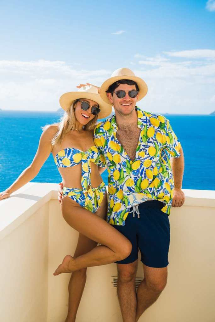 smiling couple wearing matching beachwear with hats and sunglasses
