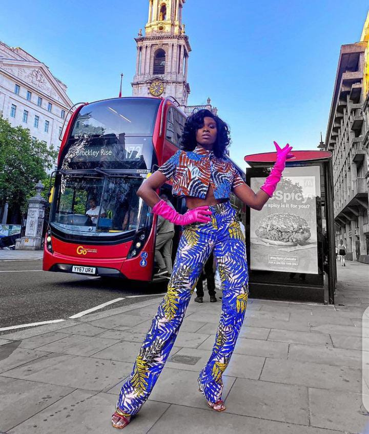 lady wearing ankara with pink gloves