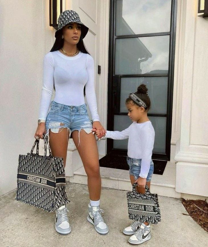 mother and daughter wearing matching tops, jean shorts and sneakers