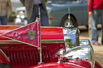 Motorhaube, Kühler und Scheinwerfer eines roten Mercedes Oldtimers