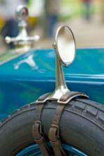 Am Reserverad mit Lederriemen befestigter Aussenspiegel eines FIAT Oltimers