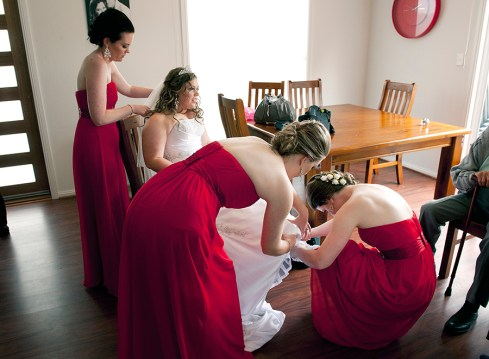 Bridesmaids helping Bride put on shoes
