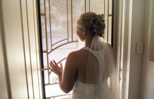 Looking out door in wedding dress
