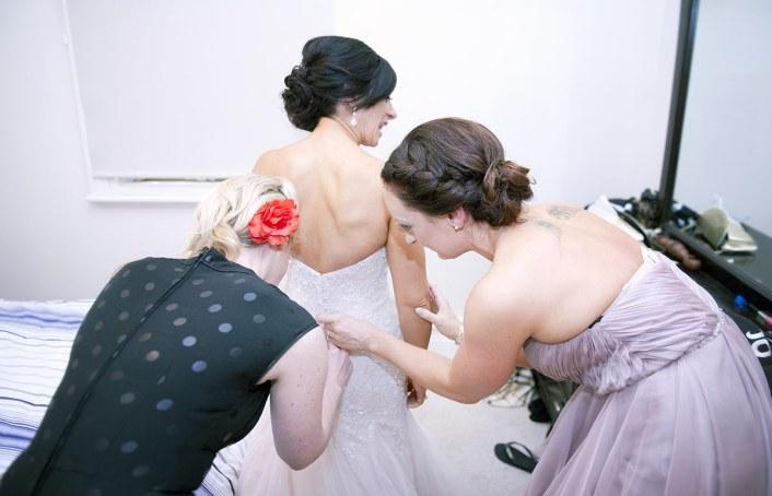 Bridal party helping put on wedding dress