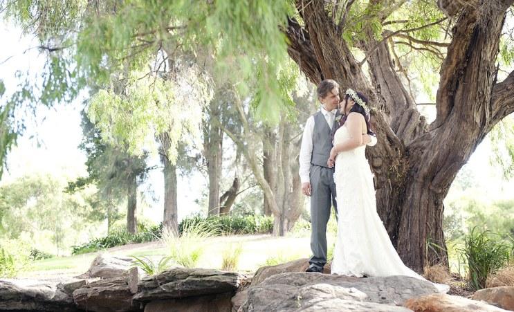 Bride and groom under tree