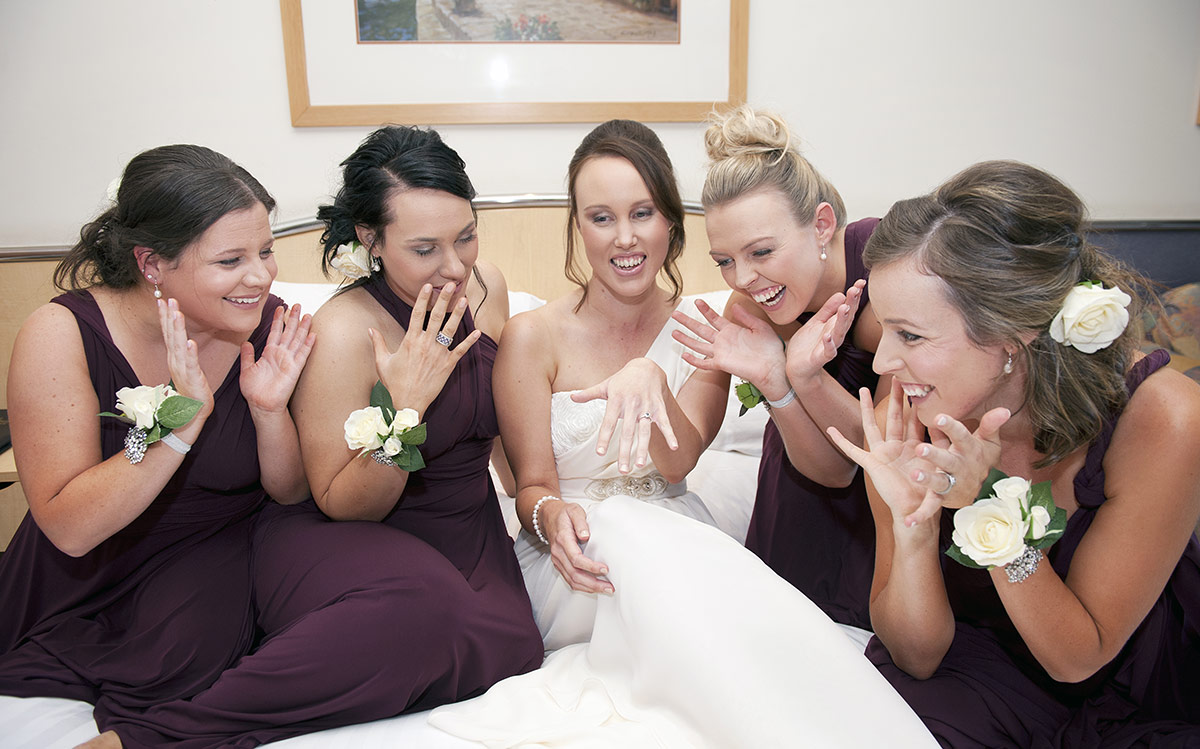 Bride and Bridesmaids looking at ring