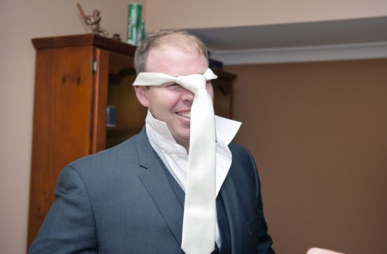 Groom having trouble with his tie