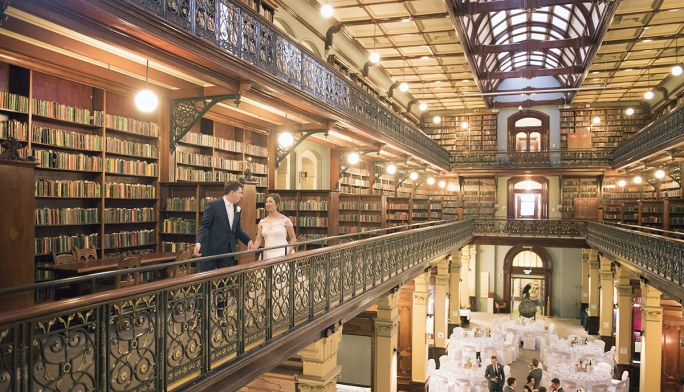 Bride and groom walking through library