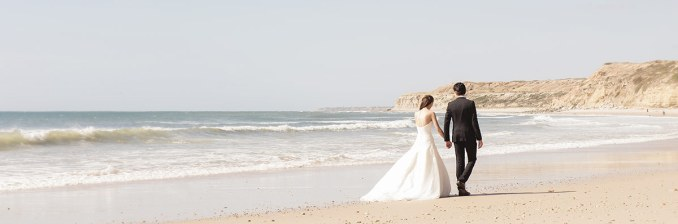 Bride and groom walking along beach