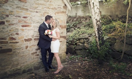 Bride and groom on stone wall