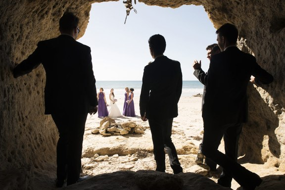 Groomsmen looking on from cave