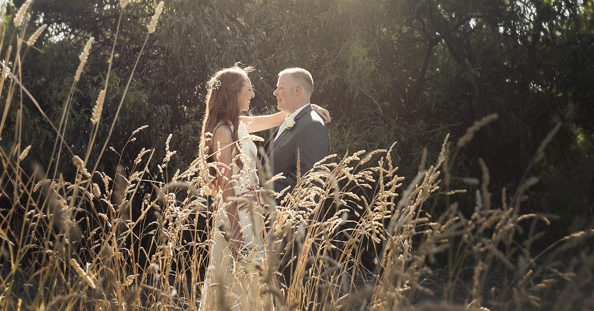 Bride and groom in the long grass