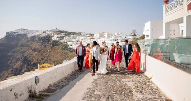 Bridal party walking together in Thera, Santorini