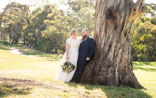 Bride and groom leaning against a tree