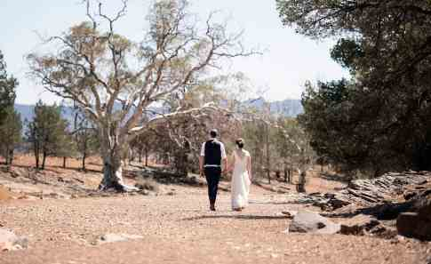 Bride and groom walking along creek on Arkapena Station