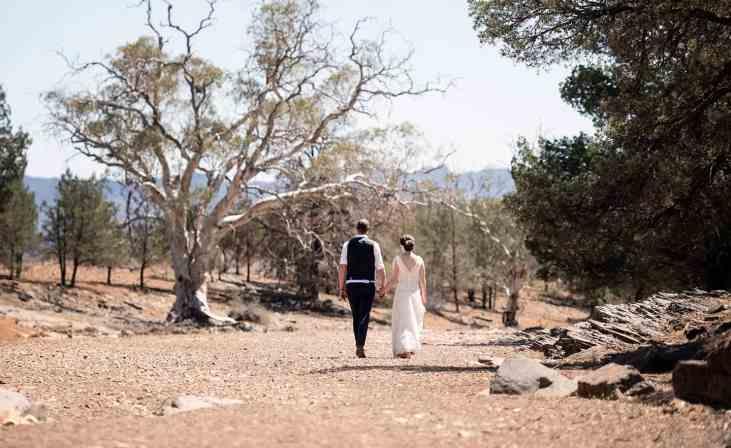 Bride and groom walking along creek on Arkapena Station