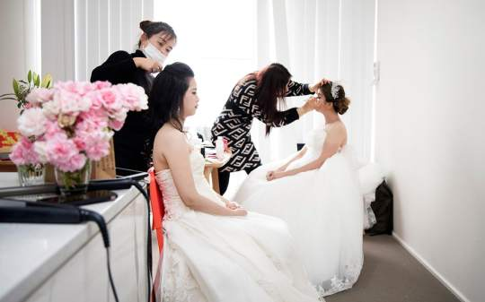 Both brides sitting in makeup chairs