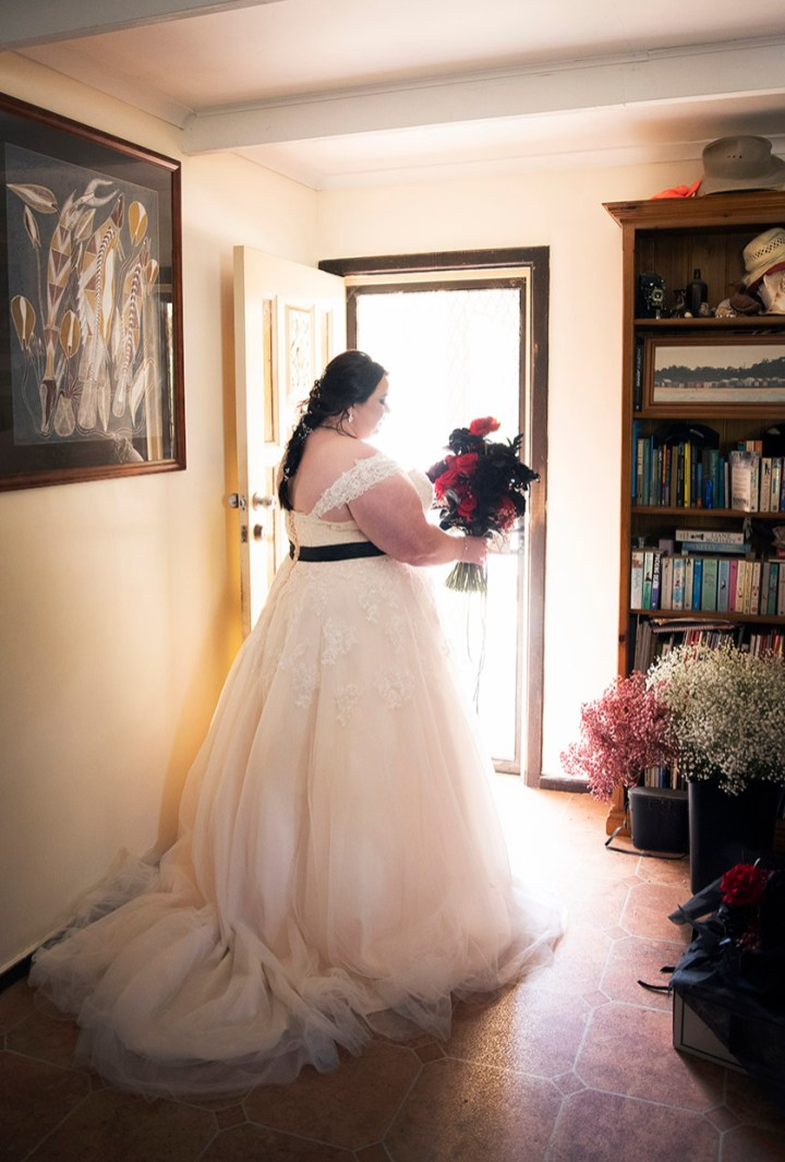 Bride standing in doorway playing with flowers