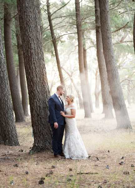 Bride and groom against a tree