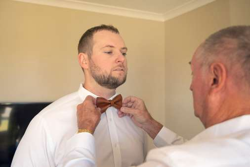 Dad putting on grooms tie