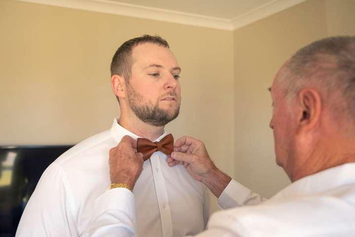 Dad putting on grooms tie