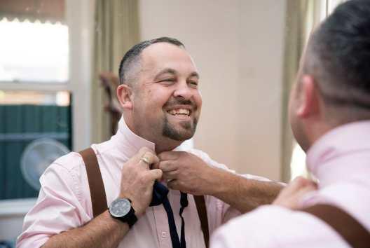 Putting on groomsman tie