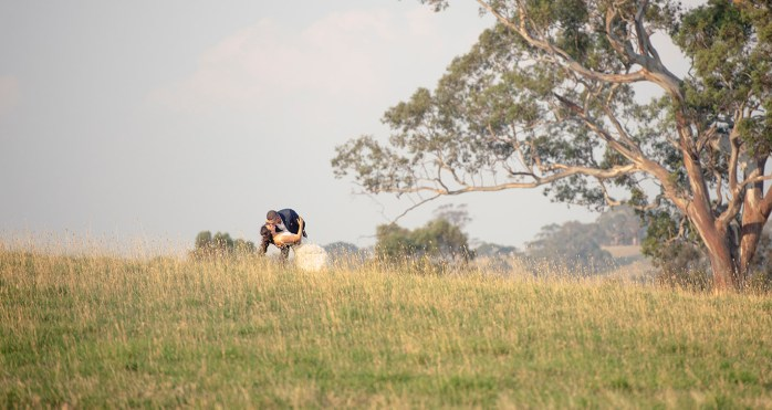 Bride and groom kissing on hill