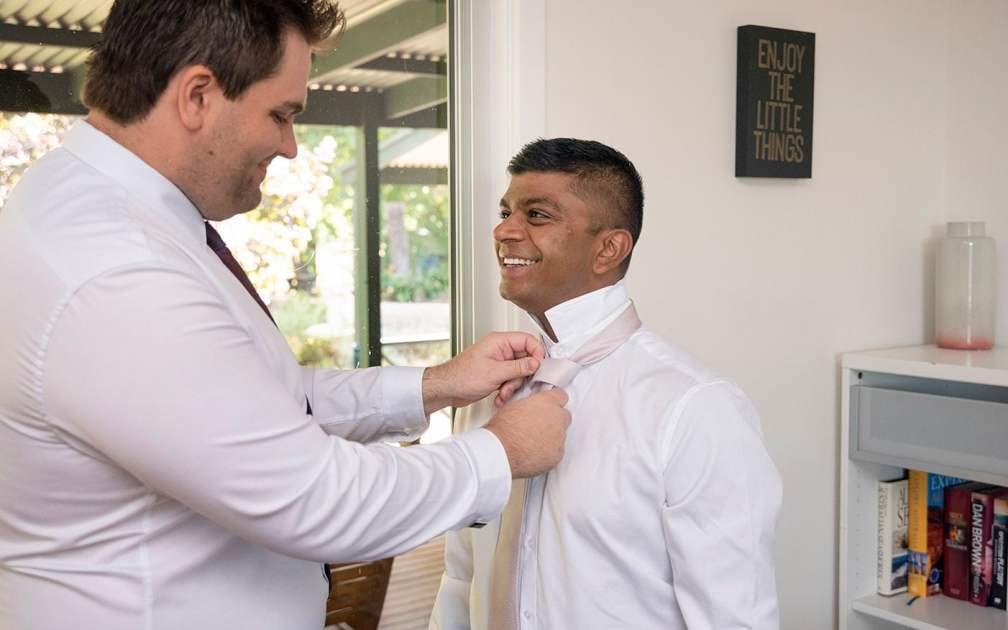 Best man putting on tie