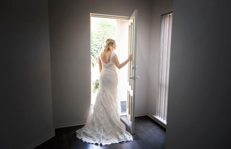 Bride leaning on door frame
