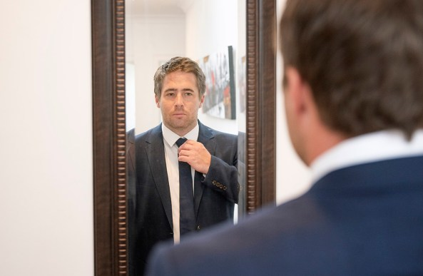 Groom looking in mirror