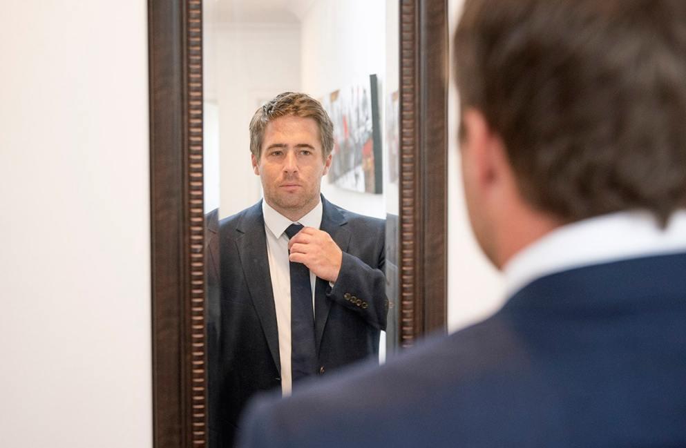 Groom looking in mirror