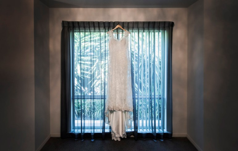 wedding dress hanging in bay window