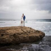 Bride and groom on the rocks on their wedding day