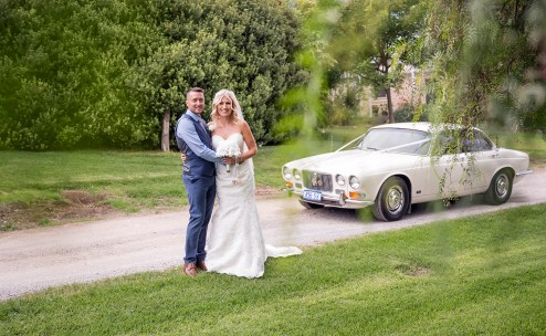 Bride and groom with the wedding car